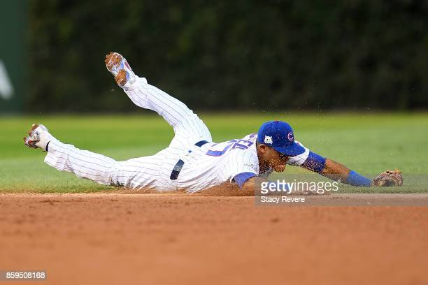 Addison Russell of the Chicago Cubs dives to field a ground ball in the seventh inning against the Washington Nationals during game three of the...