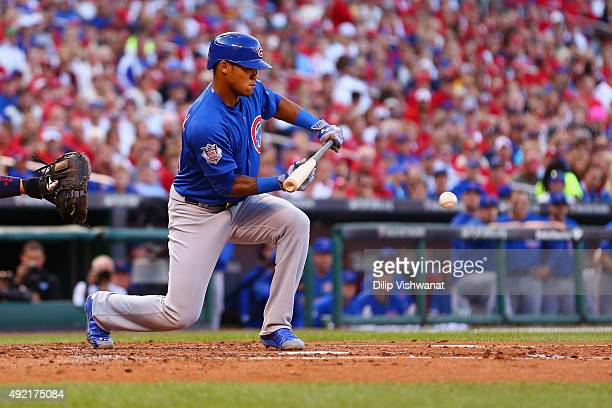 Addison Russell of the Chicago Cubs hits a sacrifice bunt to score Miguel Montero of the Chicago Cubs in the second inning against the St Louis...