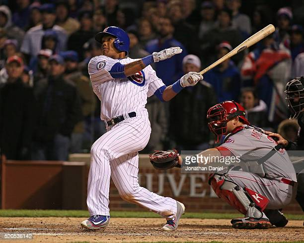 Addison Russell of the Chicago Cubs hits a threerun home run in the 8th inning against the Cincinnati Reds during the home opener at Wrigley Field on...