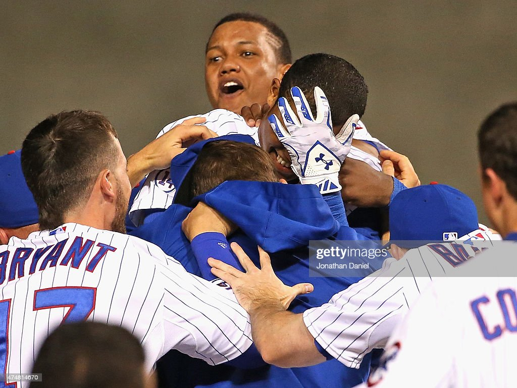Addison Russell #22 of the Chicago Cubs (center, hand on face) is mobbed by teammates after getting the game-winning hit, a double off of the center field wall, in the bttom of the 9th inning against the Washington Nationals at Wrigley Field on May 26, 2015 in Chicago, Illinois. The Cubs defeated the Nationals 3-2.