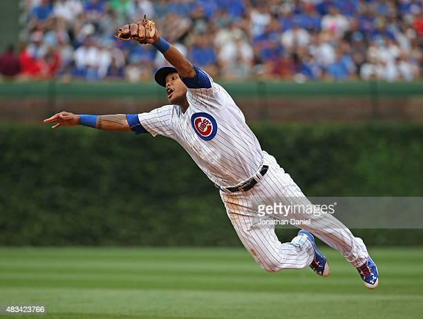 Addison Russell of the Chicago Cubs leaps to try and catch a ball hit by Hunter Pence of the San Francisco Giants in the 6th inning at Wrigley Field...