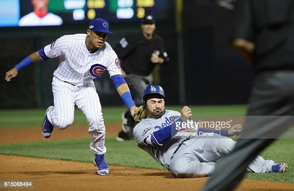 Addison Russell of the Chicago Cubs tags out Adrian Gonzalez of the Los Angeles Dodgers in the sixth inning to complete the double play during game...