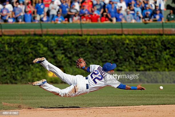 Addison Russell of the Chicago Cubs tosses the ball to Javier Baez for the final out of the game against the St Louis Cardinals at Wrigley Field on...