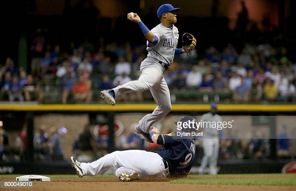 Addison Russell of the Chicago Cubs turns a double play past Manny Pina of the Milwaukee Brewers in the third inning at Miller Park on September 7...