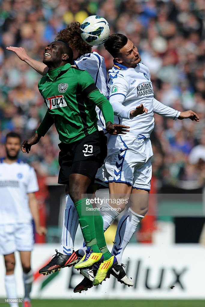 Addy Waku Menga of Muenster, Dominic Peitz and Danny Blum of Karlsruhe battle for and header during the 3. Liga match between Preussen Muenster and Karlsruher SC at Preussenstadion on April 20, 2013 in Muenster, Germany.