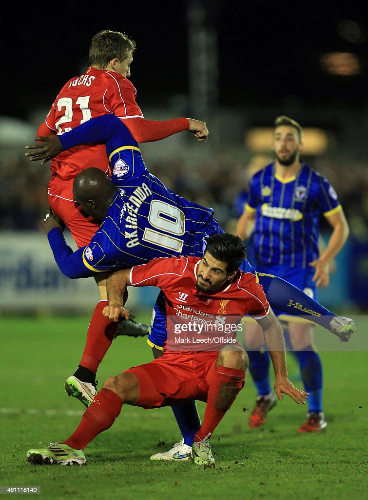 <a gi-track='captionPersonalityLinkClicked' href=/galleries/search?phrase=Adebayo+Akinfenwa&family=editorial&specificpeople=609204 ng-click='$event.stopPropagation()'>Adebayo Akinfenwa</a> of AFC Wimbledon collides with <a gi-track='captionPersonalityLinkClicked' href=/galleries/search?phrase=Lucas+Leiva+-+Defensive+Midfielder+-+Born+1987&family=editorial&specificpeople=4114250 ng-click='$event.stopPropagation()'>Lucas Leiva</a> and Emre Can of Liverpool during the FA Cup Third Round match between AFC Wimbledon and Liverpool at The Cherry Red Records Stadium on January 5, 2015 in Kingston upon Thames, England.