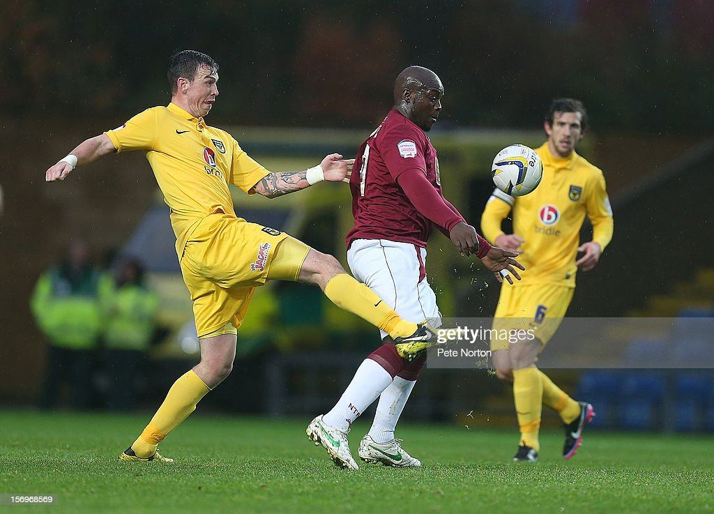 Adebayo Akinfenwa of Northampton Town attempts to control the ball under pressure from Michael Raynes of Oxford United during the npower League Two match between Oxford United and Northampton Town at Kassam Stadium on November 24, 2012 in Oxford, England.