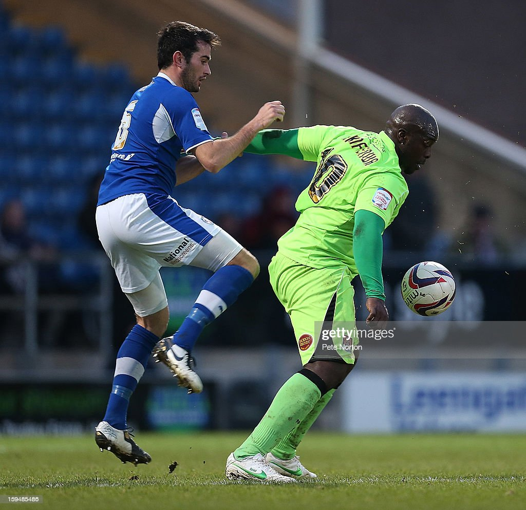 Adebayo Akinfenwa of Northampton Town attempts to control the ball under pressure from Sam Hird of Chesterfield during the npower League Two match between Chesterfield and Northampton Town at the Proact Srtadium on January 12, 2013 in Chesterfield, England.