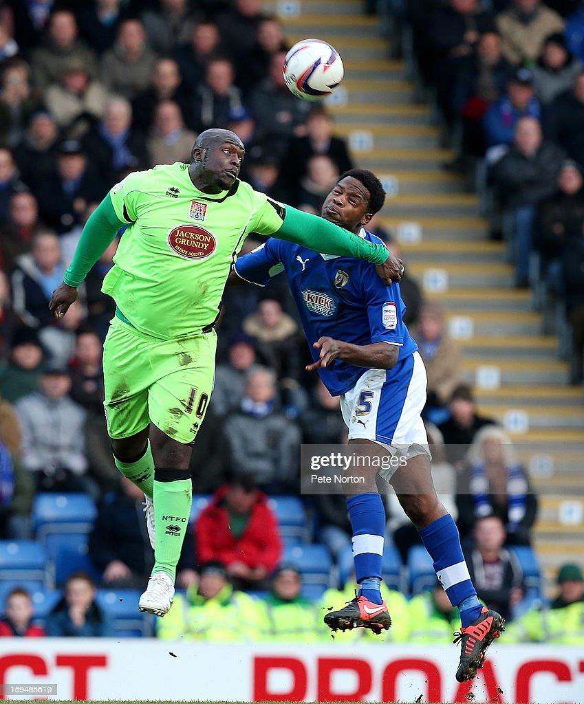 Adebayo Akinfenwa of Northampton Town challenges for the ball with Neal Trotman of Chesterfield during the npower League Two match between Chesterfield and Northampton Town at the Proact Srtadium on January 12, 2013 in Chesterfield, England.