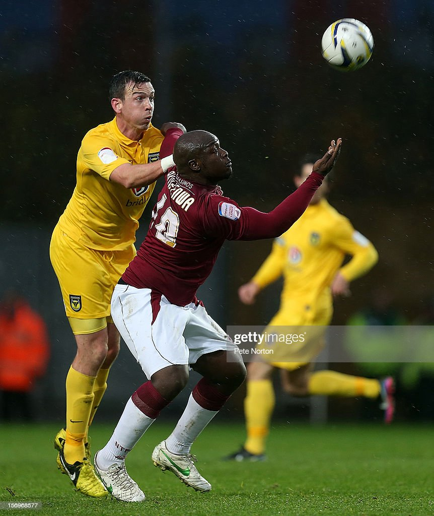 Adebayo Akinfenwa of Northampton Town looks to control the ball under pressure from Michael Raynes of Oxford United during the npower League Two match between Oxford United and Northampton Town at Kassam Stadium on November 24, 2012 in Oxford, England.