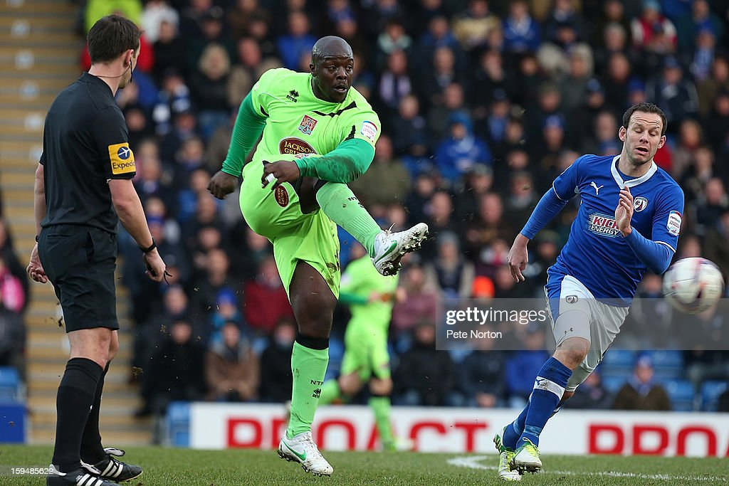 Adebayo Akinfenwa of Northampton Town plays the ball past Sam Togwell of Chesterfield during the npower League Two match between Chesterfield and Northampton Town at the Proact Srtadium on January 12, 2013 in Chesterfield, England.