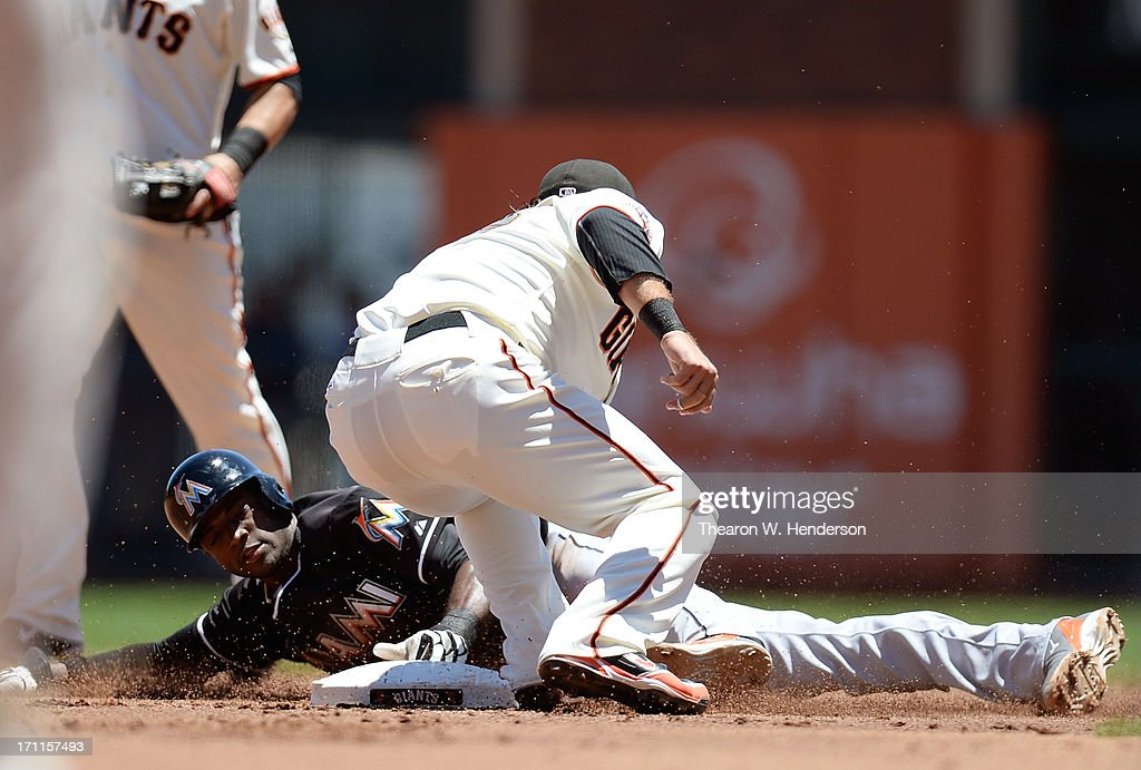 Adeiny Hechavarria #3 of the Miami Marlins gets caught stealing second, tagged out by Brandon Crawford #35 of the San Francisco Giants in the second inning at AT&T Park on June 22, 2013 in San Francisco, California.