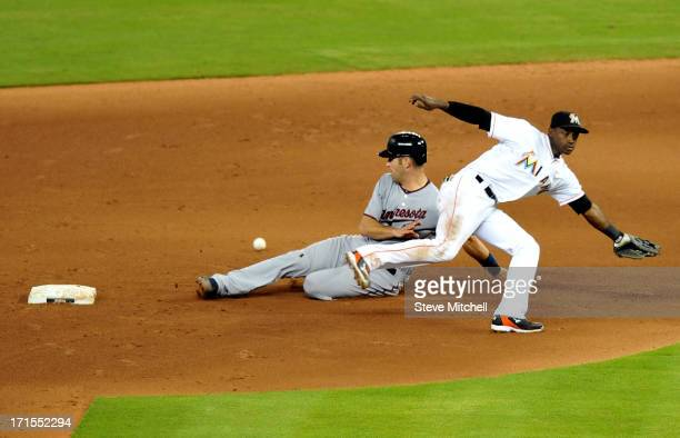 Adeiny Hechavarria of the Miami Marlins is unable to field a throw as Joe Mauer of the Minnesota Twins slides safely into second base during the...