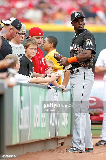 Adeiny Hechavarria of the Miami Marlins signs a few autographs prior to the start of the game against the Cincinnati Reds at Great American Ball Park...