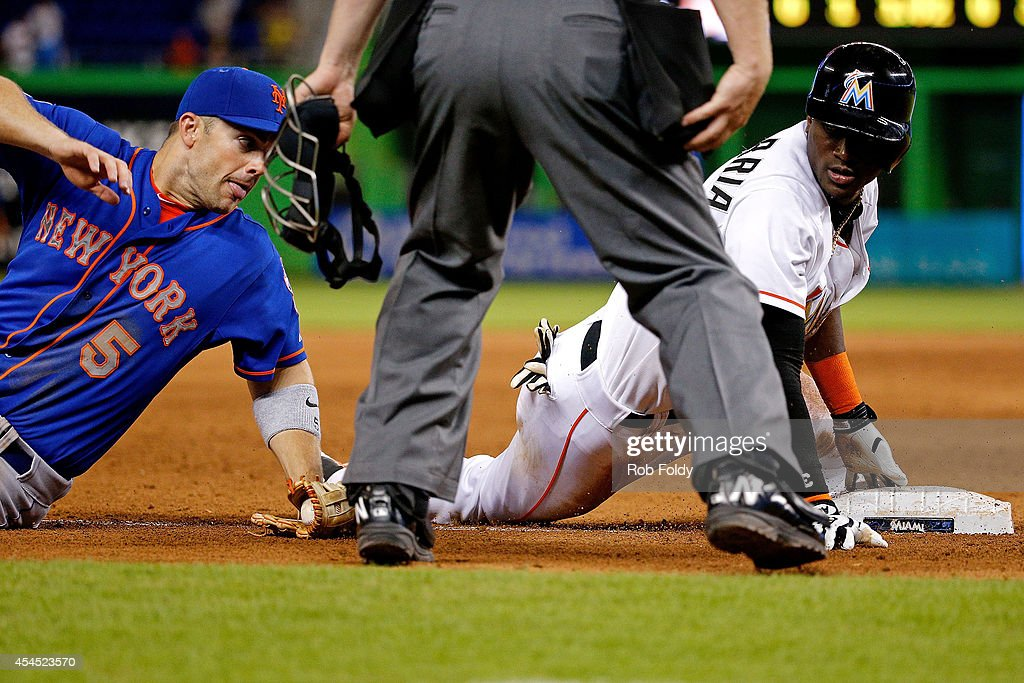Adeiny Hechavarria #3 of the Miami Marlins slides safely into third base ahead of the tag from David Wright #5 of the New York Mets during the sixth inning of the game at Marlins Park on September 2, 2014 in Miami, Florida.