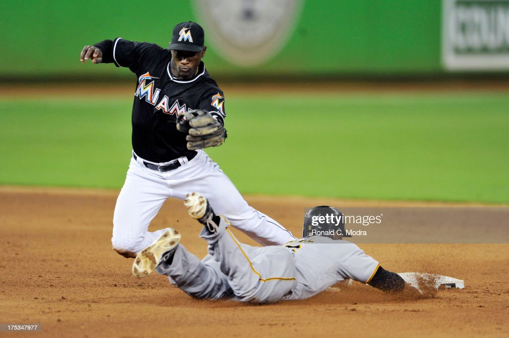 Adeiny Hechavarria #3 of the Miami Marlins takes the throw as Starling Marte #6 of the Pittsburgh Pirates steals second base during a MLB game at Marlins Park on July 26, 2013 in Miami, Florida.