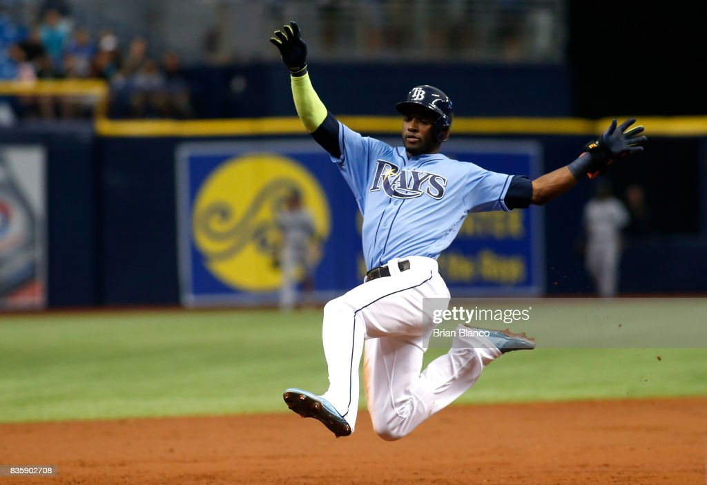 Adeiny Hechavarria #11 of the Tampa Bay Rays leaps to slide into third base after hitting a triple off of pitcher Yovani Gallardo of the Seattle Mariners during the third inning of a game on August 20, 2017 at Tropicana Field in St. Petersburg, Florida.