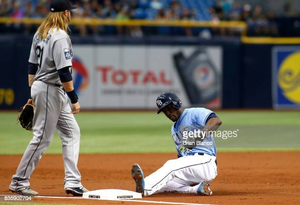 Adeiny Hechavarria of the Tampa Bay Rays slides safely into third base ahead of third baseman Taylor Motter of the Seattle Mariners during the third...