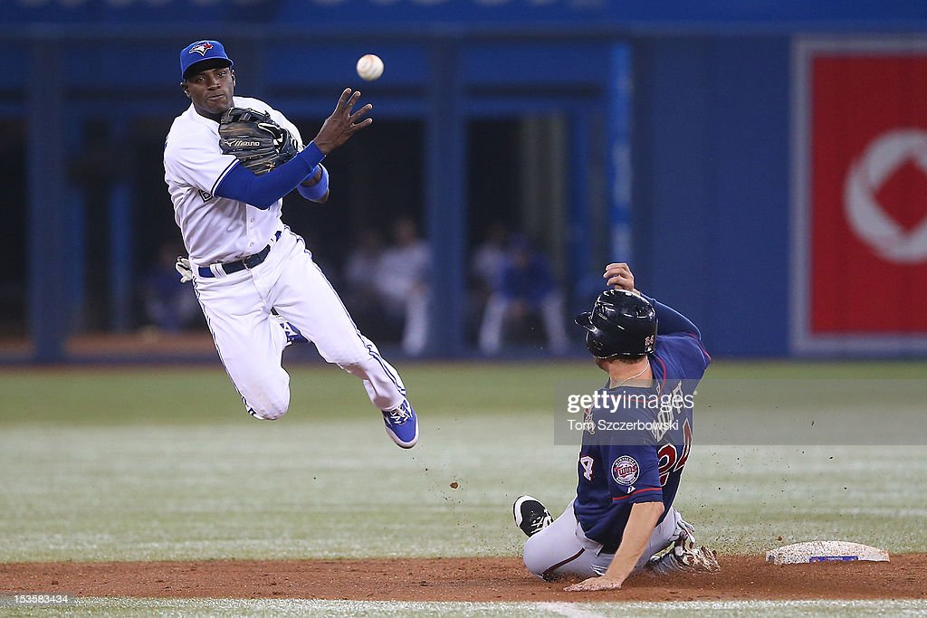 Adeiny Hechavarria #3 of the Toronto Blue Jays gets the force out at second base in the fourth inning but cannot turn a double play during MLB game action as Trevor Plouffe #24 of the Minnesota Twins slides on October 3, 2012 at Rogers Centre in Toronto, Ontario, Canada.