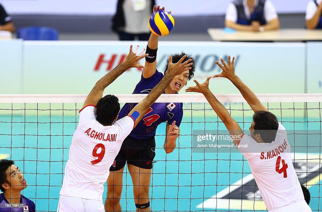 Adel Gholami (L) and Fukuzawa Tatsuya of Japan and Mir saeed Marouf during 17th Asian Men's Volleyball Championship between Iran And Japan on October 5, 2013 in Dubai, United Arab Emirates.