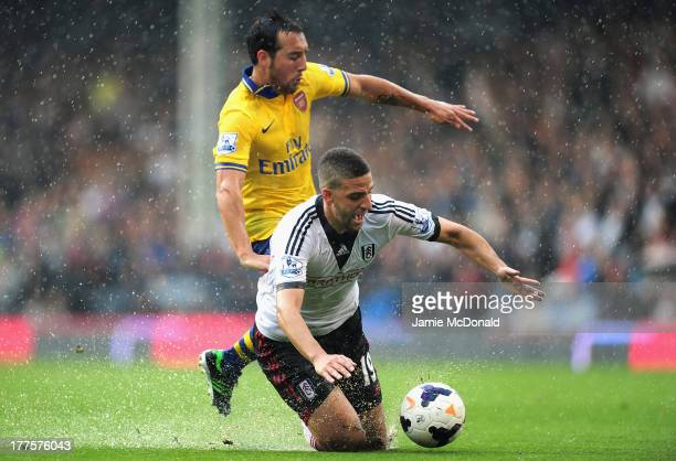 Adel Taarabt of Fulham and Santi Cazorla of Arsenal battle for the ball during the Barclays Premier League match between Fulham and Arsenal at Craven...