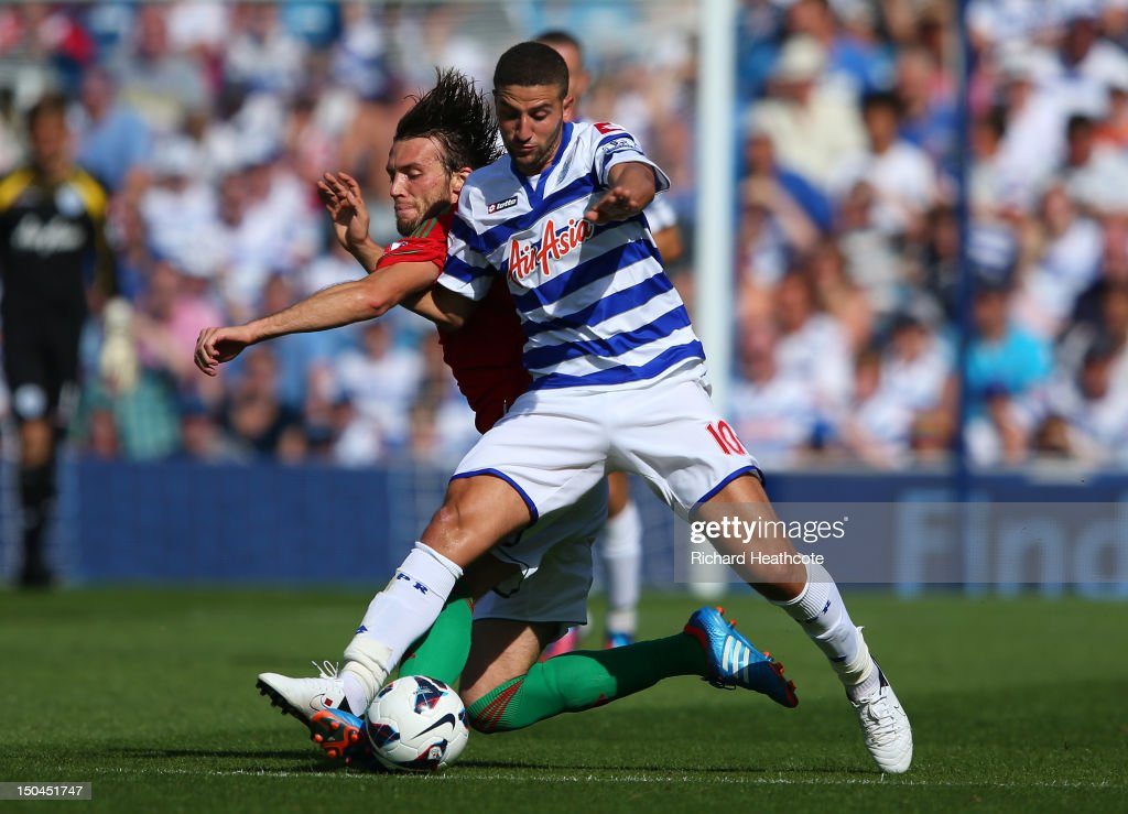 <a gi-track='captionPersonalityLinkClicked' href=/galleries/search?phrase=Adel+Taarabt&family=editorial&specificpeople=3275547 ng-click='$event.stopPropagation()'>Adel Taarabt</a> of QPR is tackled by Michu of Swansea during the Barclays Premier League match between Queens Park Rangers and Swansea City at Loftus Road on August 18, 2012 in London, England.