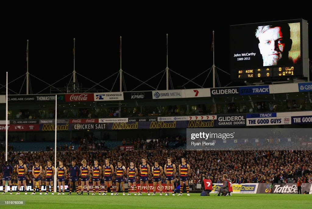 Adelaide and Fremantle players pause for a minutes silence in honour of John McCarthy of Port Adelaide before the AFL Second Semi Final match between the Adelaide Crows and the Fremantle Dockers at AAMI Stadium on September 14, 2012 in Adelaide, Australia.