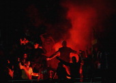 Adelaide fans light a flare after their team scored a goal during the round 14 ALeague match between the Melbhourne Victory and Adelaide United at...