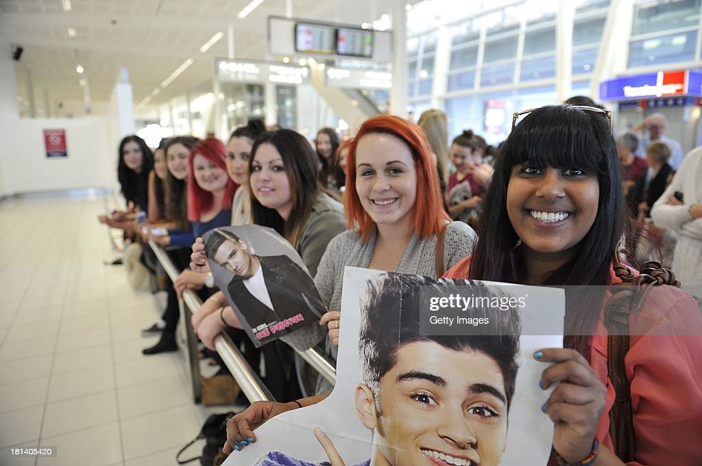 Adelaide fans of One Direction (R to L) Priyani Melville- Smith22 yo and Zoe Wright 18yo wait patiently at Adelaide Airport for their idols to arrive on September 21, 2013 in Adelaide, Australia.