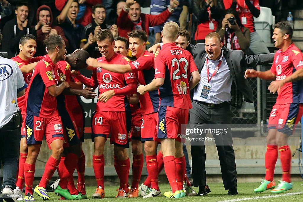 Adelaide players and coach Josep Gombau celebrates after a goal by Bruce Djite during the round 24 A-League match between Adelaide United and Sydney FC at Coopers Stadium on March 21, 2014 in Adelaide, Australia.