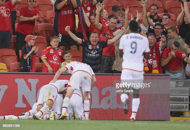Adelaide players celebrate with fans after the winning goal during the round two ALeague match between the Brisbane Roar and Adelaide United at...