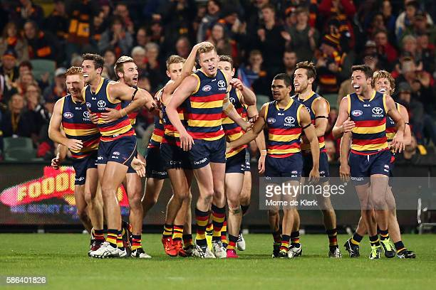 Adelaide players congratulate teammate Reilly O'Brien after he kicked his first goal during the round 20 AFL match between the Adelaide Crows and the...