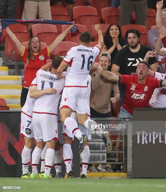Adelaide team mates celebrate the equaliser during the round two ALeague match between the Brisbane Roar and Adelaide United at Suncorp Stadium on...