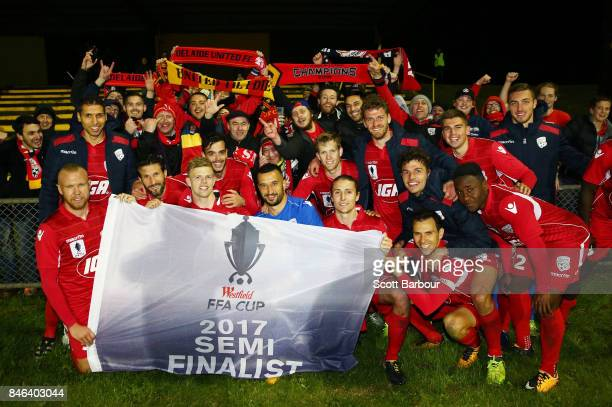 Adelaide United pose with the Westfield FFA Cup semi final qualification flag and their supporters in the crowd after winning the FFA Cup Quarter...