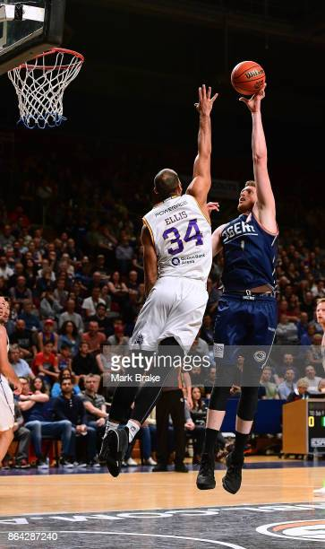 Adelaide's Matthew Hodgson goes for the basket defended by Sydneys's Perry Elis during the round three NBL match between the Adelaide 36ers and the...