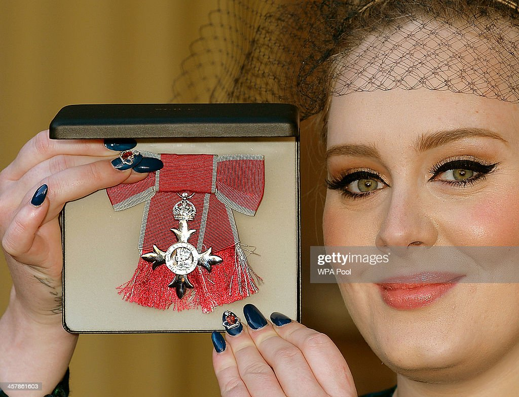 Adele Adkins MBE holds her MBE award for services to music after it was presented to her by the Prince of Wales at an Investiture ceremony at Buckingham Palace on December 19, 2013 in London, England.