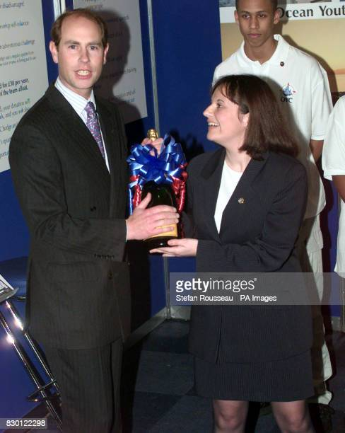 Adele Harwood Young Achiever with the Ocean Youth Club hands Prince Edward a magnum of champagne to toast his recent engagement to Sophie Rhys Jones...