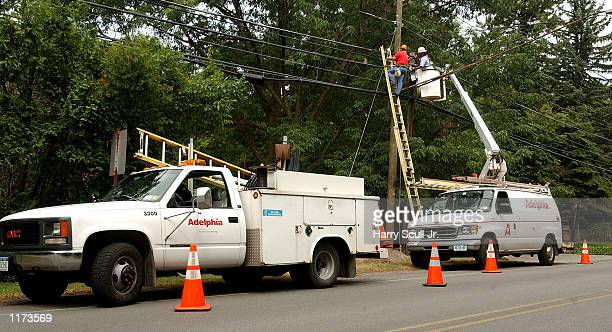Adelphia Cable employees work on cable lines July 25 2002 in Clarence New York Former CEO of Adelphia Communications John Rigas and his two sons were...