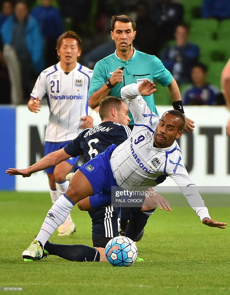 Ademilson of Gamba Osaka (front) is tackled by Leigh Broxham of Melbourne Victory during the AFC Champions League football match between Melbourne Victory and Gamba Osaka in Melbourne on May 3, 2016. / AFP / Paul Crock / IMAGE