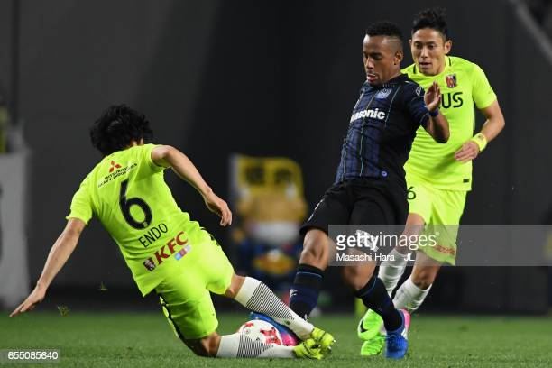 Ademilson of Gamba Osaka is tackled by Wataru Endo of Urawa Red Diamonds during the JLeague J1 match between Gamba Osaka and Urawa Red Diamonds at...