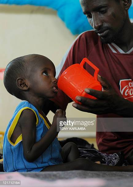 Aden a threeyearold Somali refugee with his father Abdille is fed at the stabilisation centre at Hagadere refugee area on August 2 2011 where he is...
