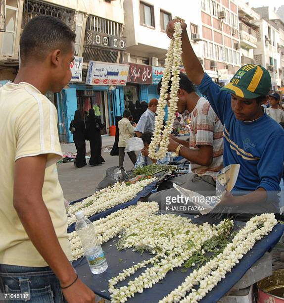 TO GO WITH AFP FEATURE BY KHALED FAZAA Yemeni younths sell necklaces made of local jasmine flowers in one of the shopping districts of Yemen's...