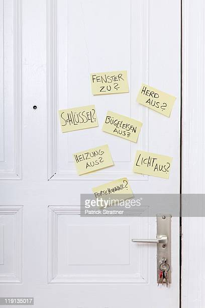Adhesive notes on a front door with various reminders in German