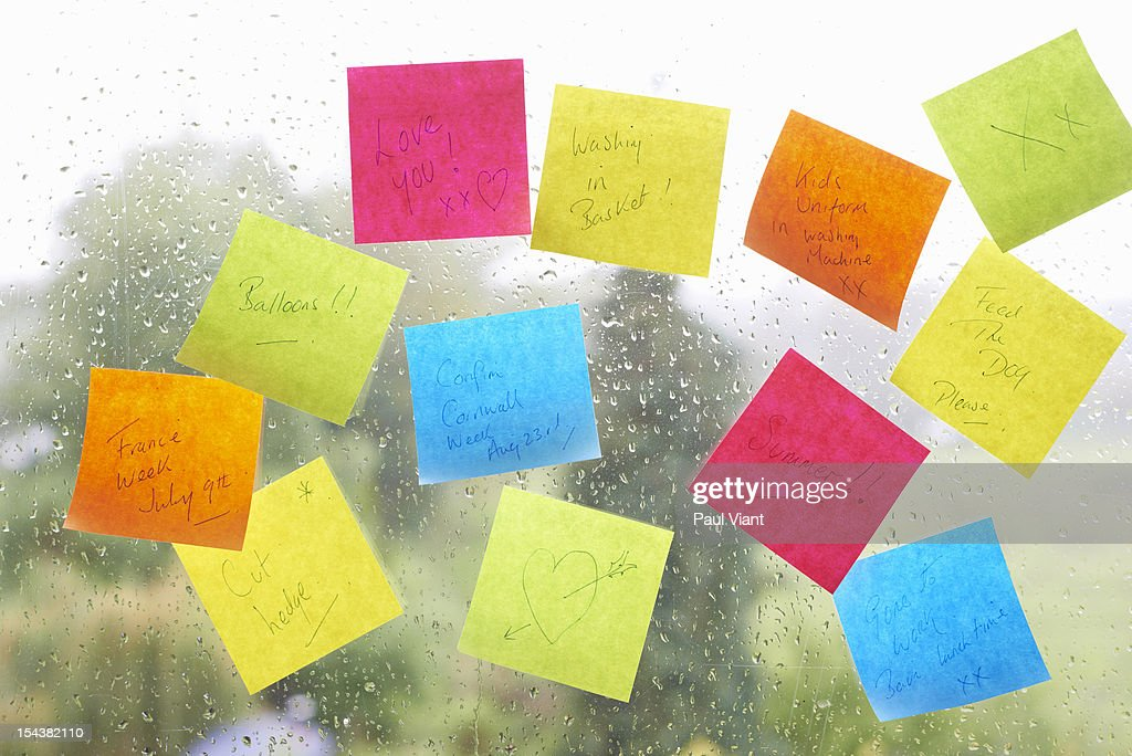 adhesive notes stuck to window pane : Stock Photo