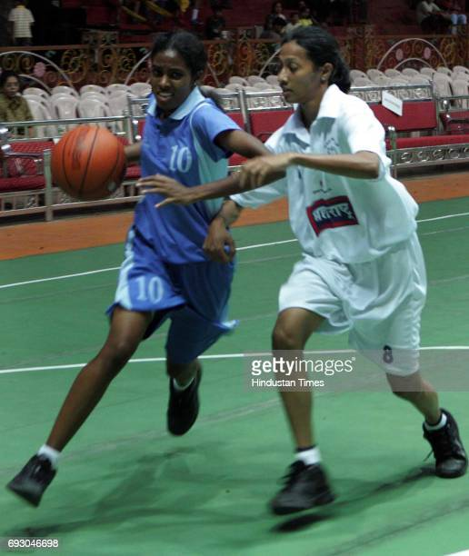 Adhirai of Southern Railway takes control of the ball from Lincy Jose of Maharashtra in the league match of the Savio Cup Allindia Basketball...