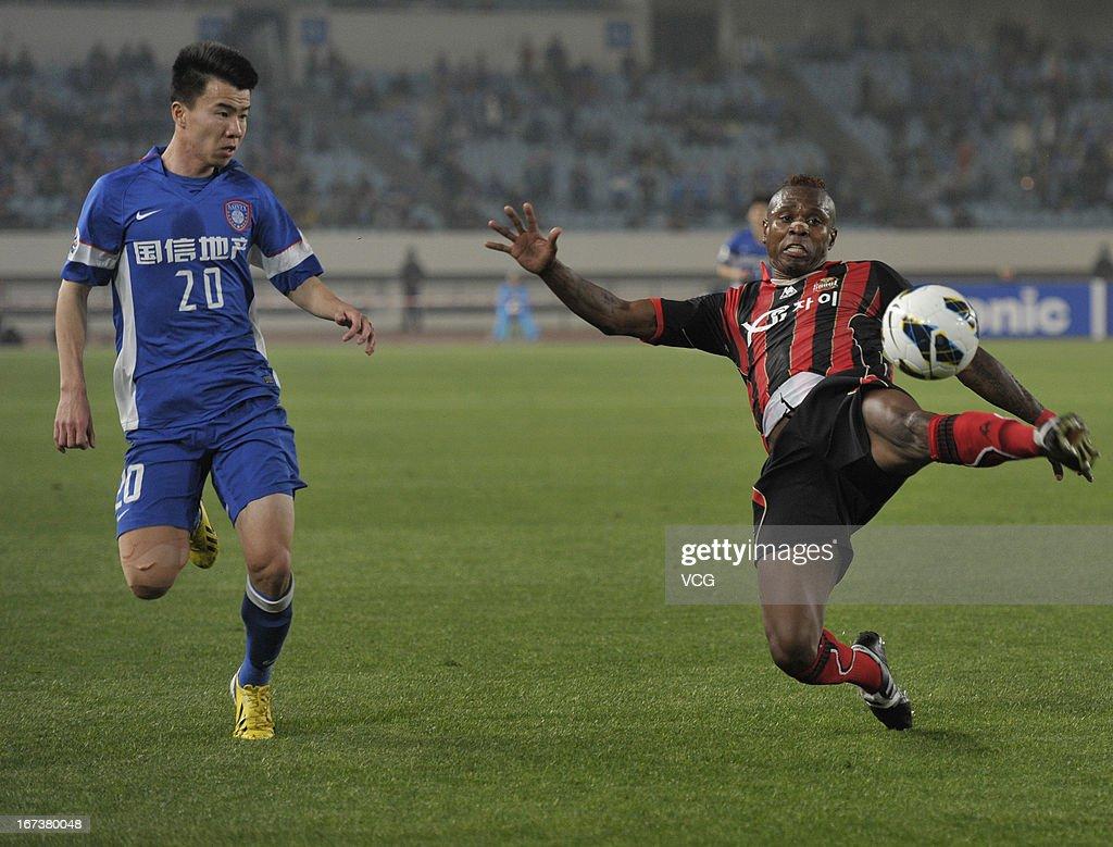Adi #8 of FC Seoul passes the ball against Sun Ke #20 of Jiangsu Sainty during the AFC Champions League match between Jiangsu Sainty and FC Seoul at Nanjing Olympic Sports Center Stadium on April 24, 2013 in Nanjing, China.
