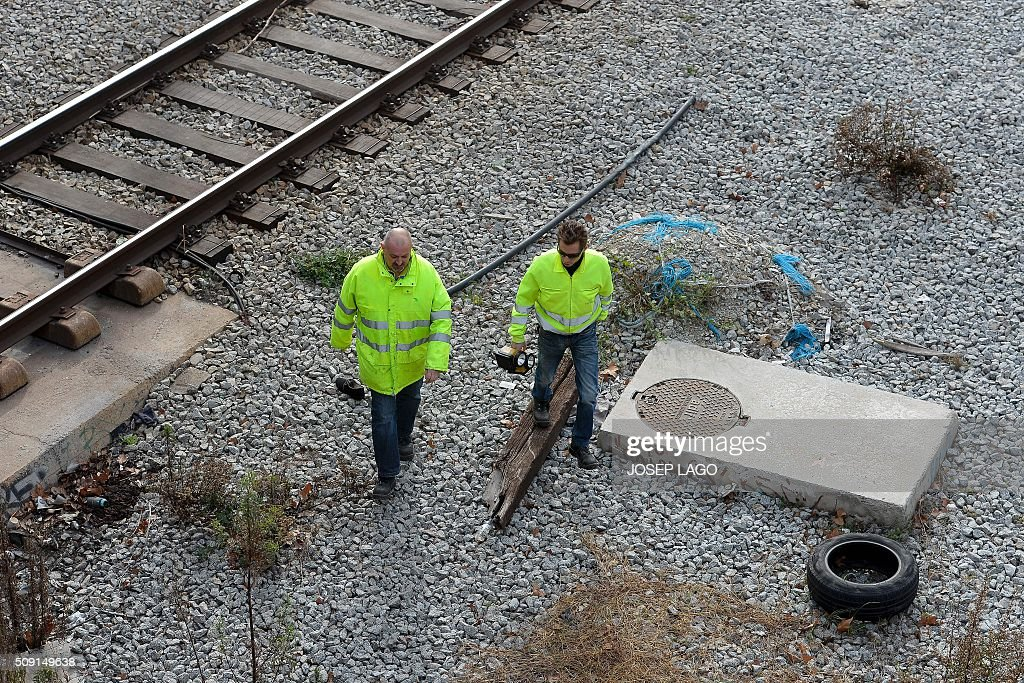 Adif Spanish railway company workers walk on railway tracks following a fire at an abandoned underground station in Barcelona on February 9, 2016. Barcelona's railway network was brought to a standstill for several hours today affecting some 72,000 passengers during rush hour after a fire brokeout in an unused subway station. / AFP / JOSEP LAGO