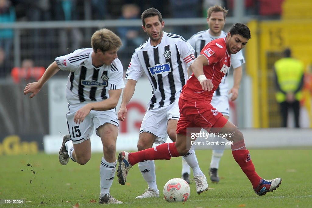 Adil Chihi of Cologne is challenged by Daniel Buballa and Leandro Grech of Aalen during the Second Bundesliga match between VfR Aalen and 1 FC Koeln...