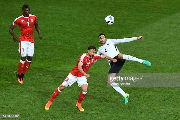 Adil Rami of France attempts an overhead kick while Admir Mehmedi of Switzerland tries to block during the UEFA EURO 2016 Group A match between...