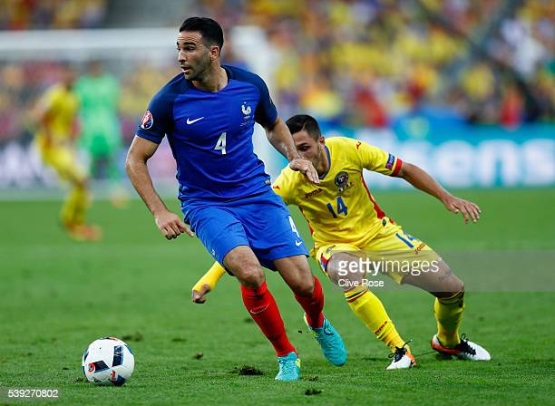 Adil Rami of France controls the ball under pressure of Florin Andone of Romania during the UEFA Euro 2016 Group A match between France and Romania...